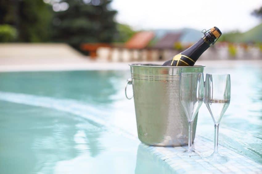 Imagem de champanhe em balde de gelo com duas taças ao lado.