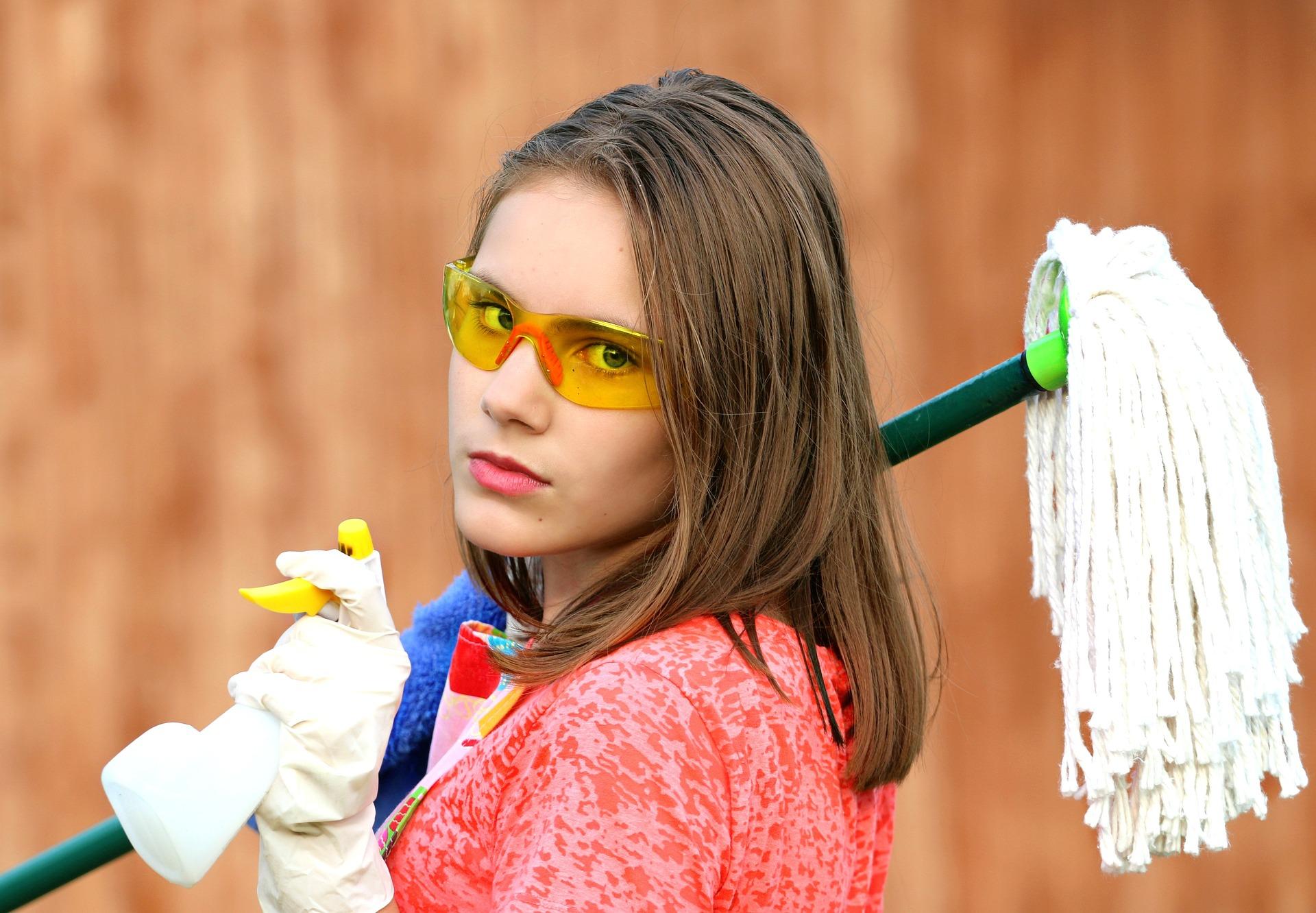 Imagem de mulher usando óculos e luvas de proteção, segurando um rodinho e um desinfetante