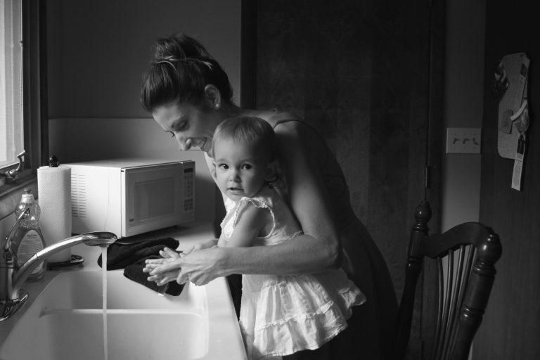 Imagem mostra uma mulher e uma criança em frente a uma torneira com água corrente.
