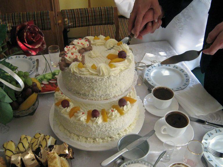 Imagem de casal cortando bolo de casamento de dois andares decorado com frutas