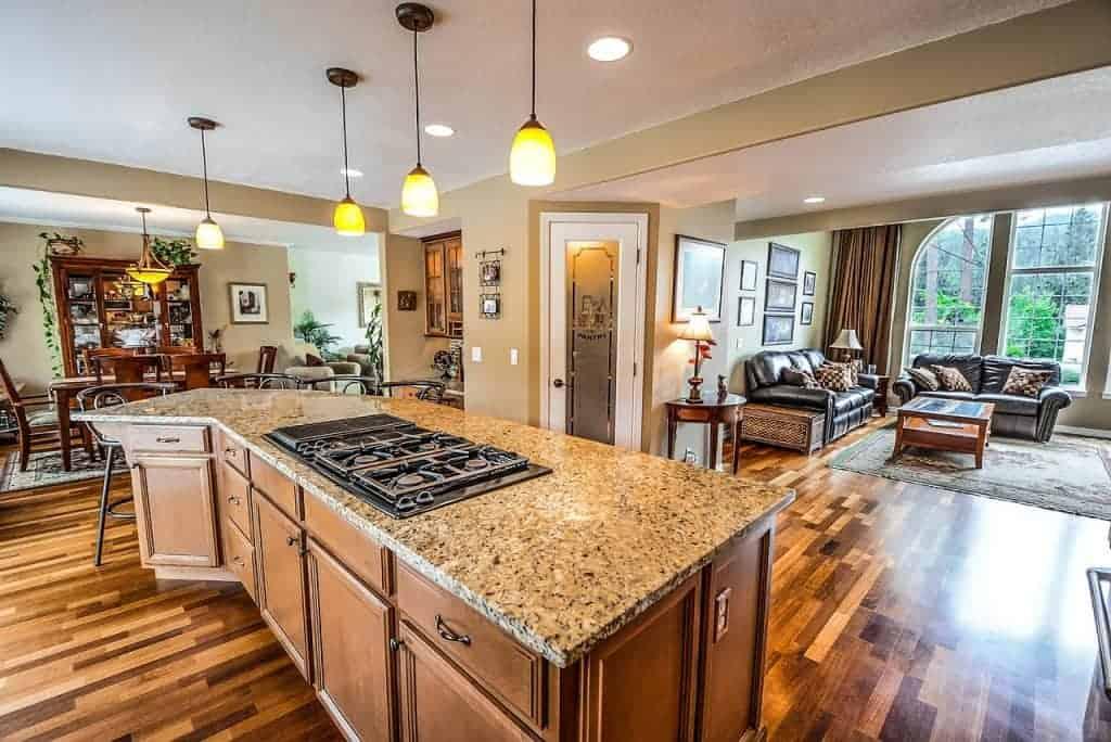 Cozinha de conceito aberto para a sala, com ilha e cooktop.