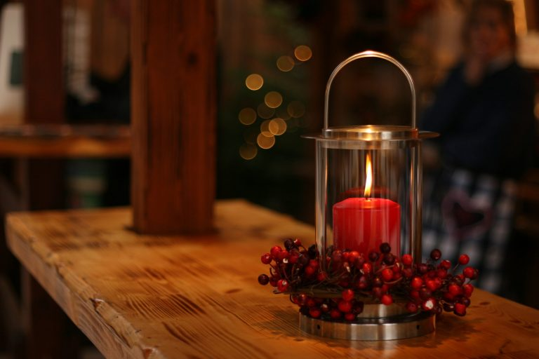 Na foto uma vela vermelha acesa em cima de uma superfície de madeira.
