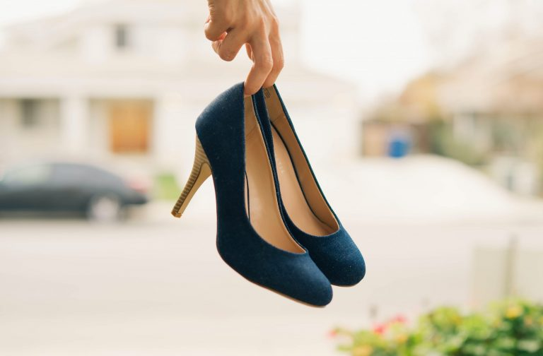 Imagem de uma mulher segurando um par de sapatos de salto alto.