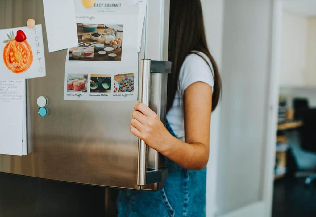Imagem mostra uma pessoa abrindo a porta de um freezer vertical.