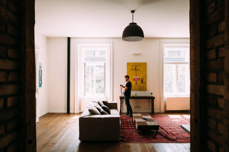Imagem de homem em sala de estar com luminária de teto em destaque