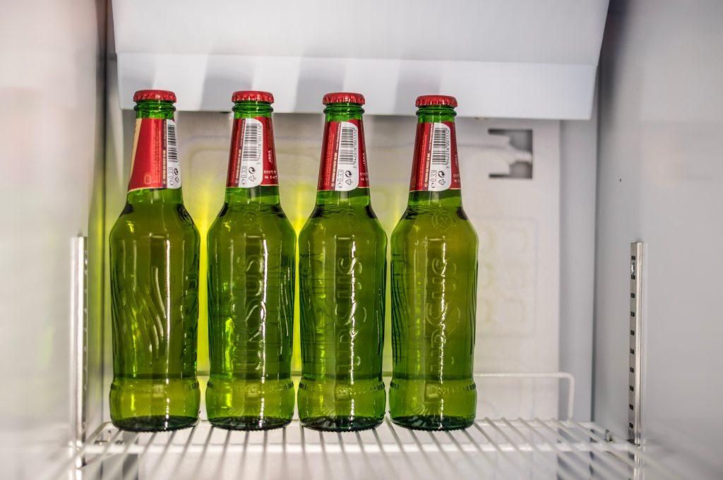 Quatro garrafas long neck dentro do congelador.