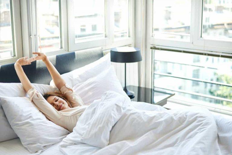 Mulher se espreguiçando na cama com abajur ao lado.