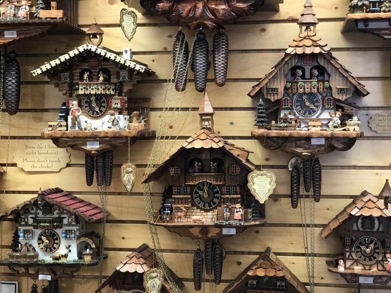 Imagem de parede de madeira com vários relógios cuco em exposição