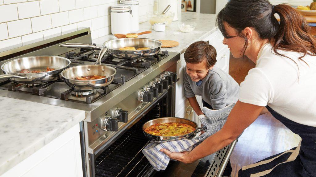 Imagem de uma mulher colocando um refratário no forno.