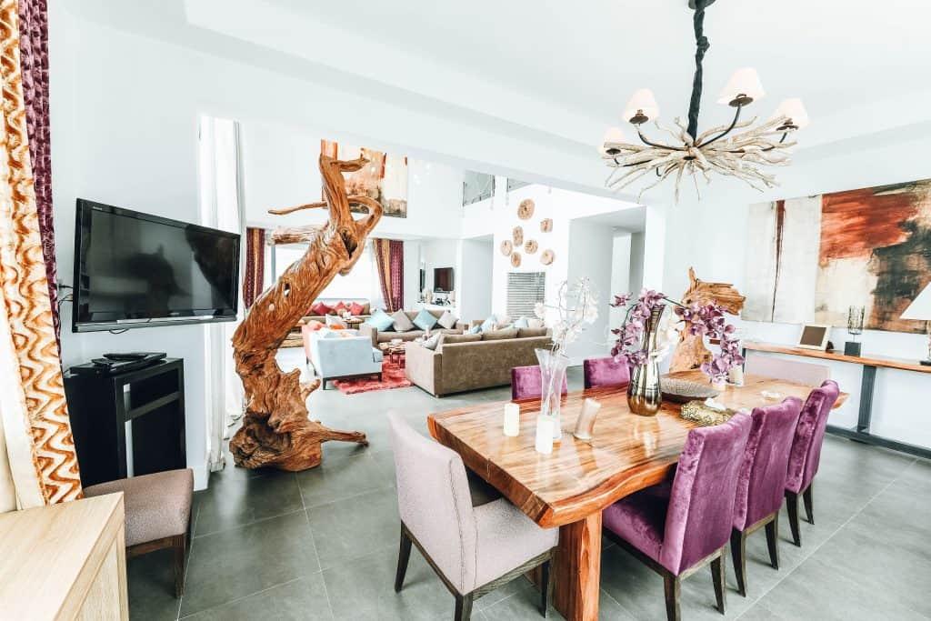 Imagem de lustre rústico feito em madeira em sala com elementos modernos.
