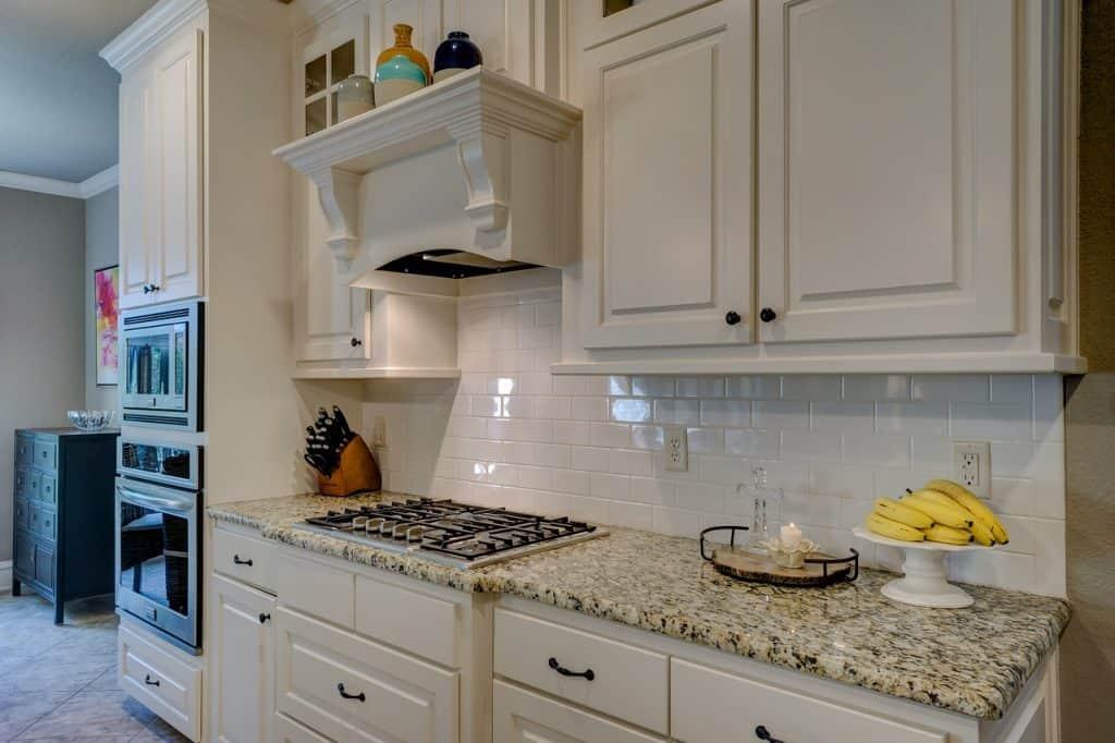 Cozinha branca com cooktop na bancada.