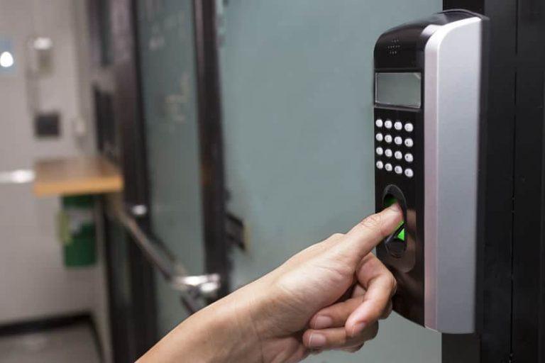 Pessoa usando a fechadura biométrica para leitura de impressão digital.