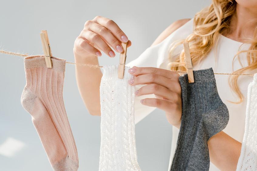 Na foto uma mulher colocando meias em um varal.