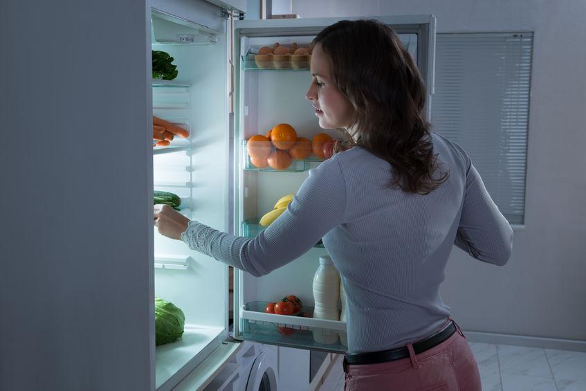 Imagem de uma mulher pegando um alimento na geladeira.