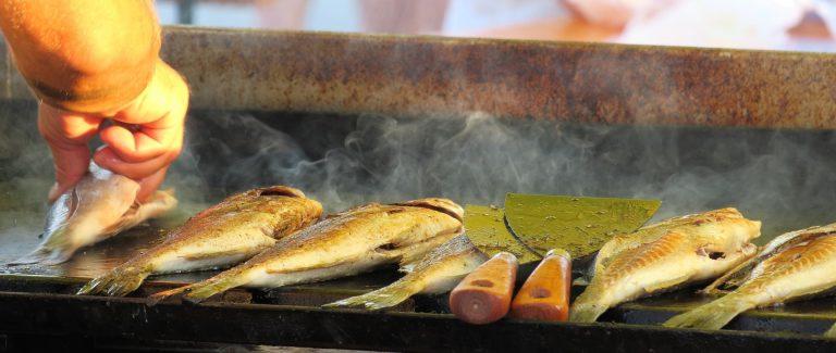 Imagem de homem colocando peixes para fritar em uma chapa de ferro fundido