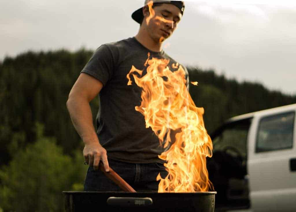 Imagem mostra um homem cuidando do fogo em frente a uma churrasqueira.