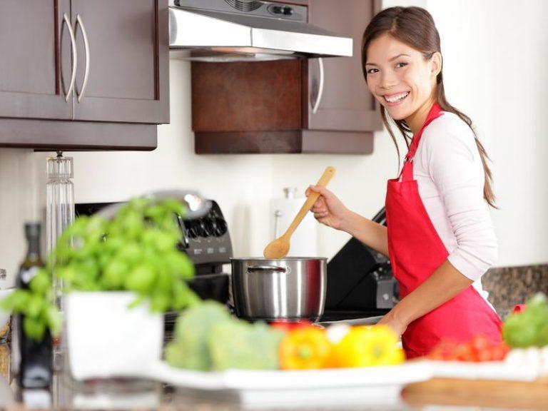 Mulher sorri para foro enquanto mexe receita em caçarola