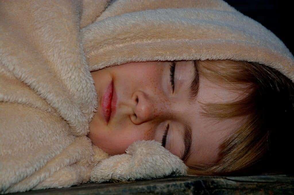 Imagem de criança deitada e coberta com um cobertor de microfibra marrom
