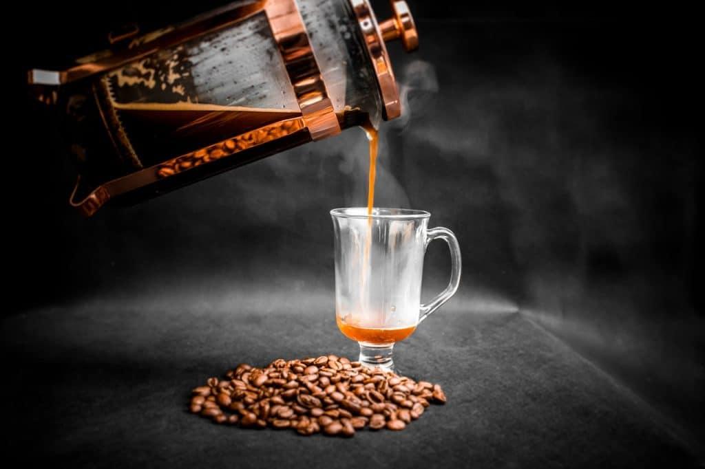 Imagem de café em cafeteira sendo despejado em xícara com grãos de café na frente.