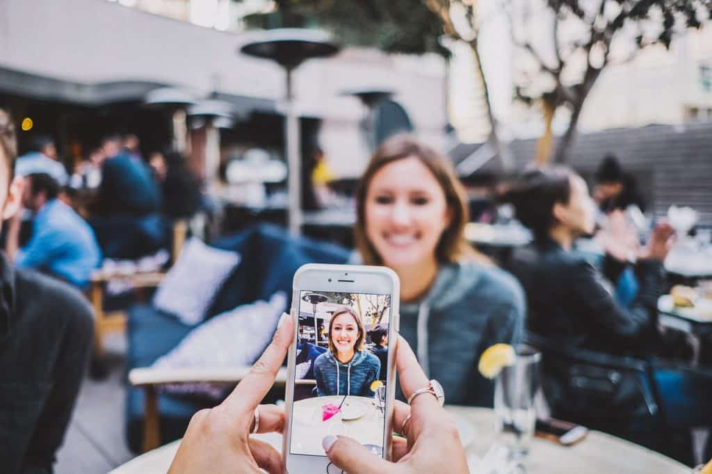 Imagem de pessoa tirando foto de uma mulher em seu celular