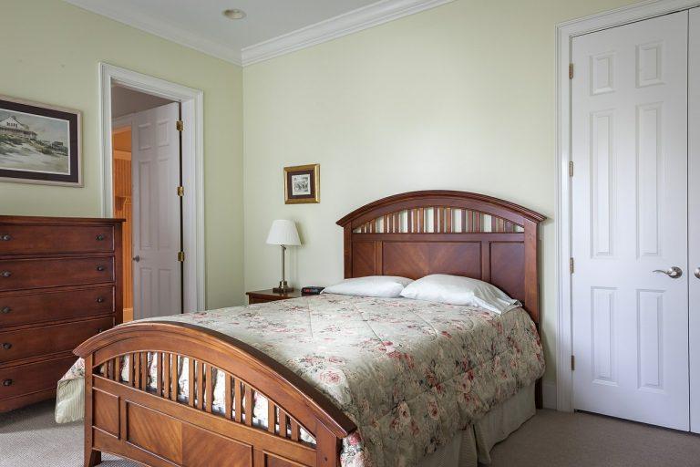 Imagem de quarto com cama queen coberta por edredom com estampa florida