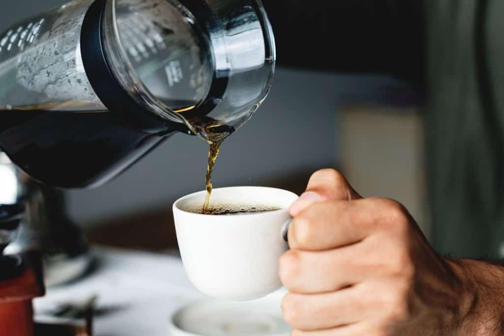 Foto de pessoa segurando jarra de café preto e despejando em xícara.