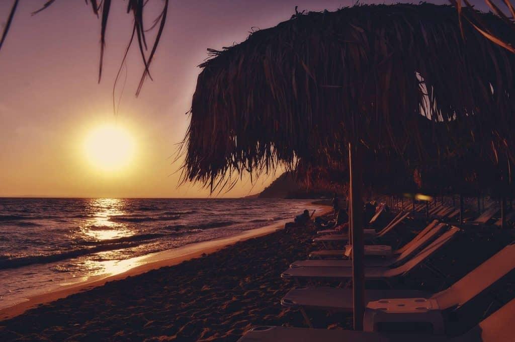 Imagem de espreguiçadeiras posicionadas em fila em uma praia, durante o pôr-do-sol.