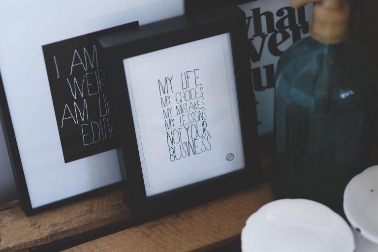 Imagem de três porta-retratos com mensagens sobre mesa de madeira com dispenser de vidro ao lado