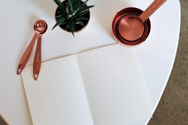 Imagem de colheres medidoras com cor de cobre sobre mesa com planta