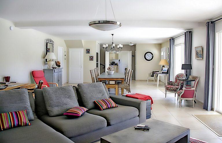 Imagem de sala de estar e copa com diferentes luminárias de teto