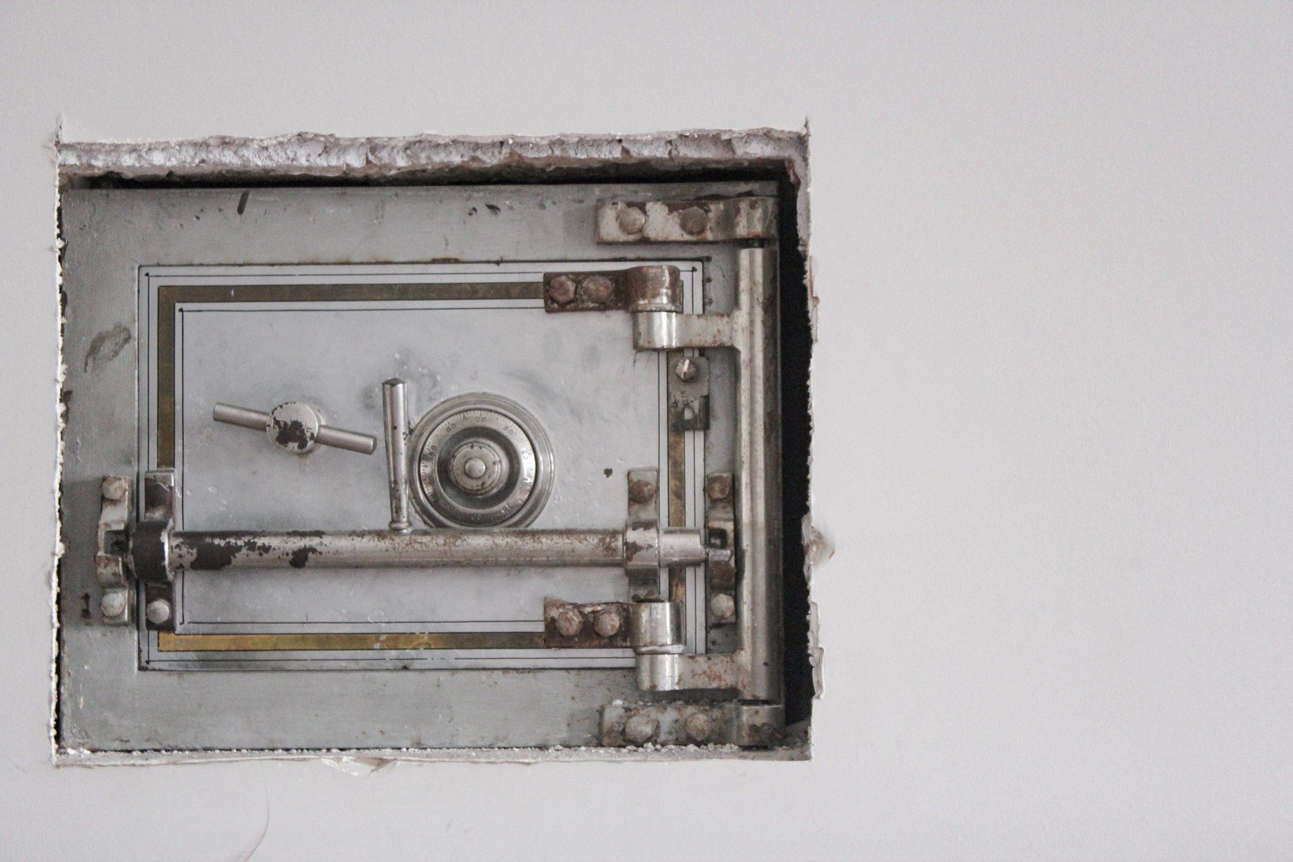 Imagem mostra um buraco numa parede, que revela um cofre mecânico embutido.