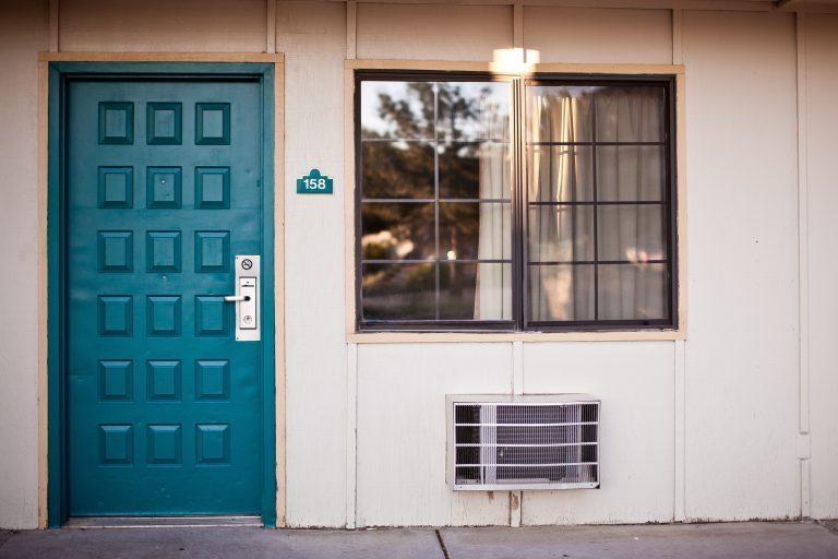 Foto de uma casa de parede branca, com uma janela, uma saída de ar condicionado, e uma porta verde, com maçaneta de inox e olho mágico no centro.