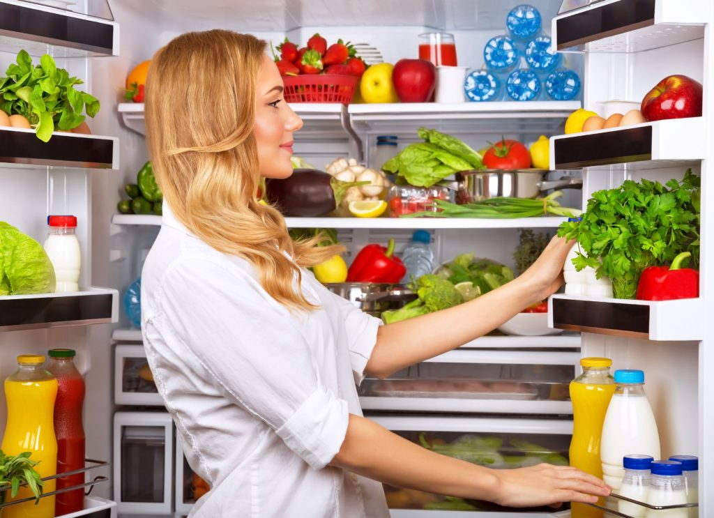 Mulher olhando para geladeira aberta.