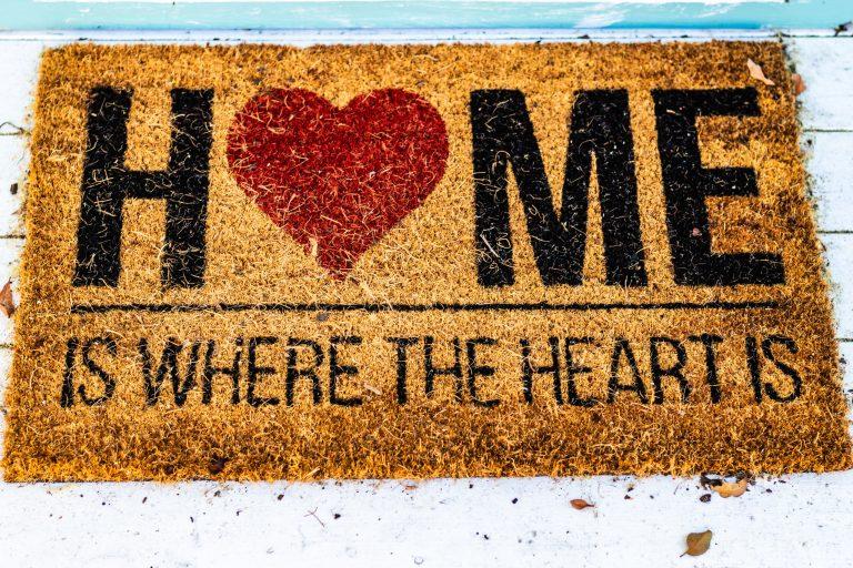 Imagem de capacho marrom com estampa com coração e mensagem de boas-vindas