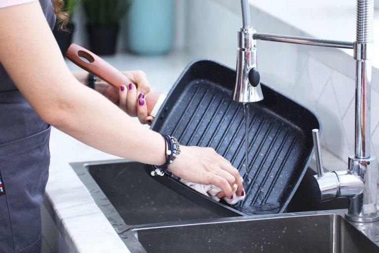 Imagem de uma pessoa lavando uma bistequeira.