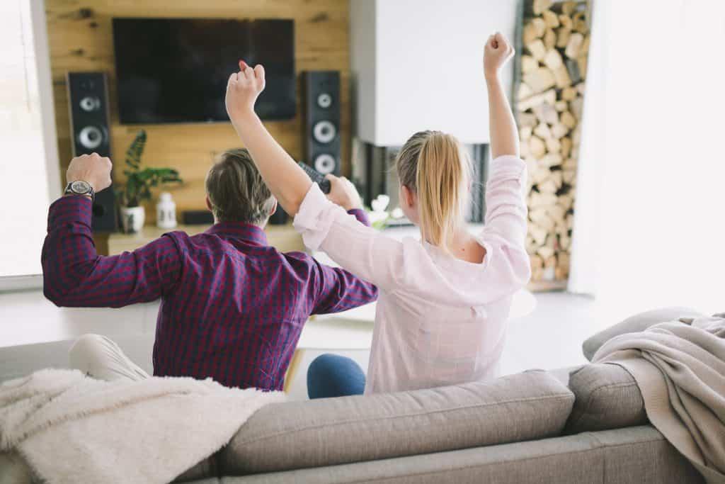 Casal vibra em frente a TV instalada em estante de madeira.