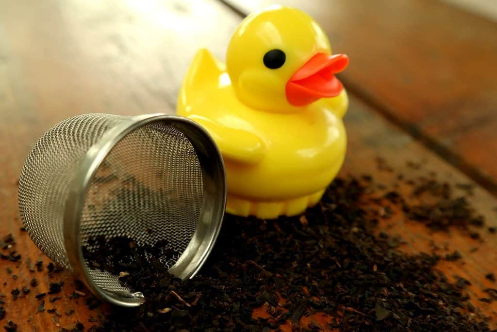 Imagem de infusor de chá metálico ao lado de infusor de plástico em formato de pato sobre mesa com chá moído.