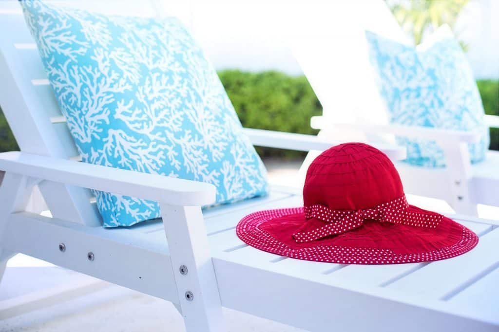 Imagem de espreguiçadeira branca com almofada azul. Sobre a espreguiçadeira há um chapéu vermelho feminino.