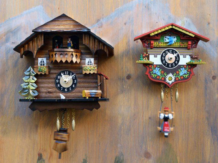 Imagem de dois relógios cuco de diferentes tamanhos colocados lado a lado