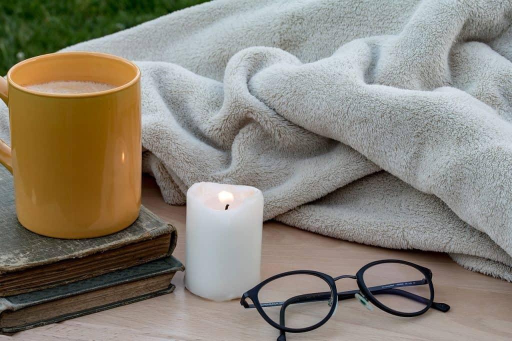 Imagem de caneca, livros, vela, óculos e cobertor de microfibra