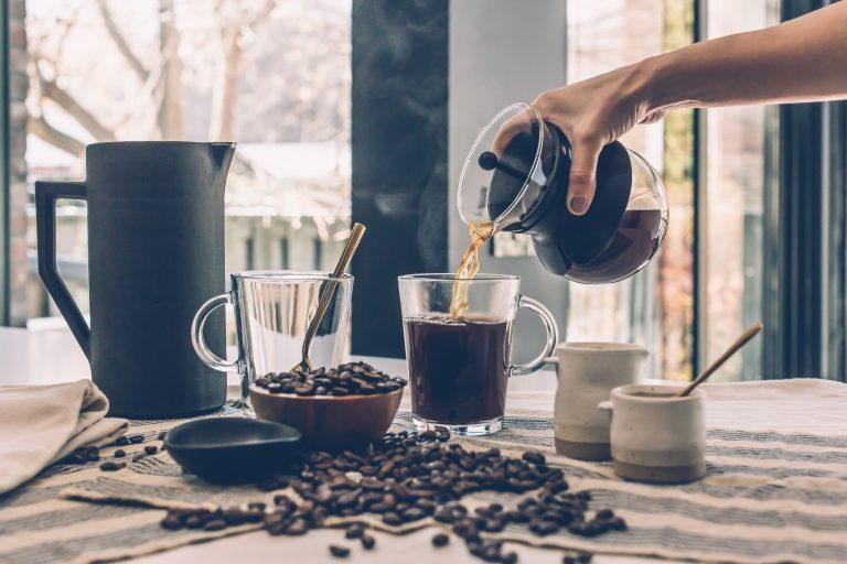 Foto de uma mão feminina servindo um café em uma xícara de vidro, em uma mesa com vários grãos de café espalhados, outros potinhos também com café, uma jarra preta e uma segunda xícara de vidro vazia.