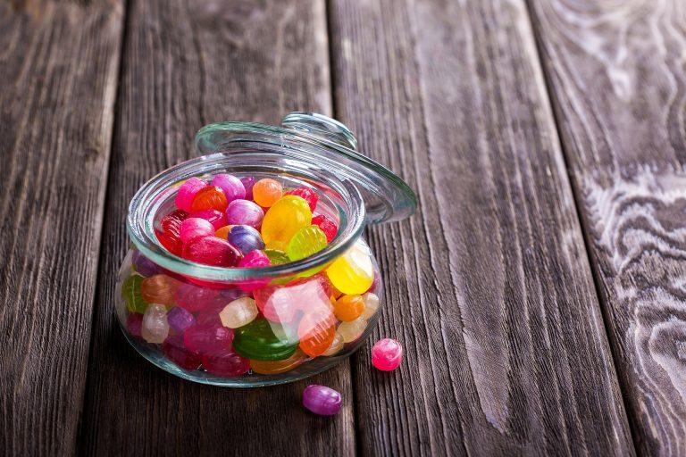 Baleiro de vidro com tampa repleto de balas coloridas sobre mesa de madeira