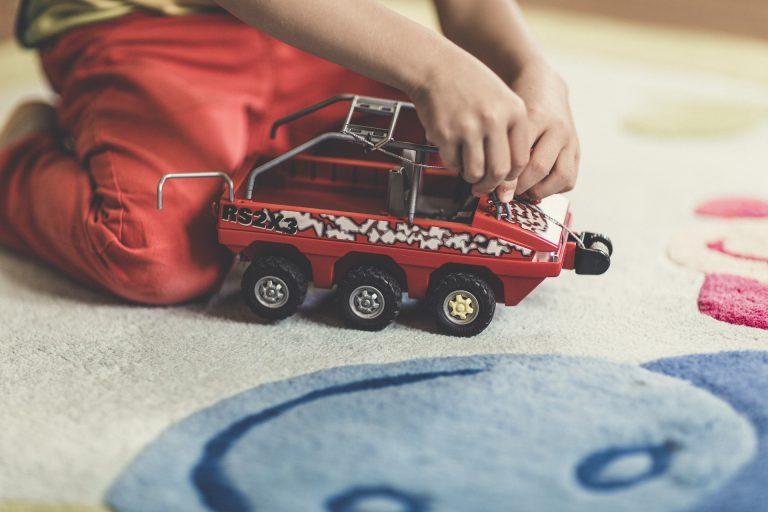 Uma criança com uma miniatura de carro nas mãos brincando em cima de um tapete.