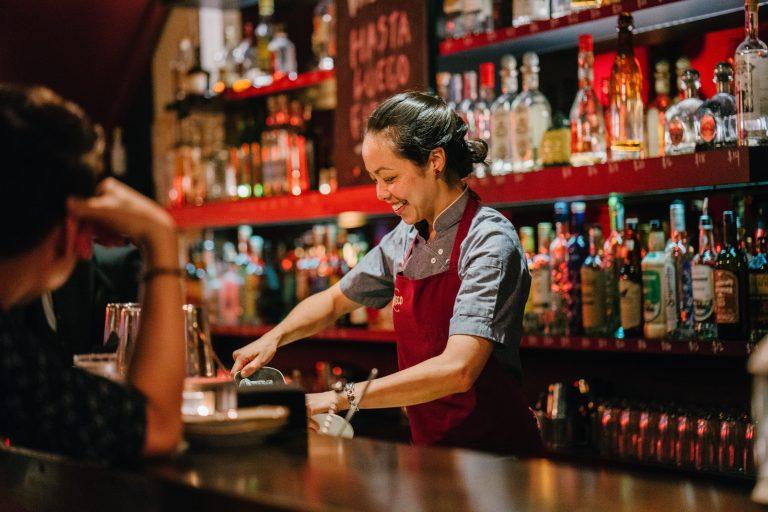 Foto de uma mulher em uma bancada de uma bar, com várias garrafas de bebidas ao fundo, olhando pra baixo e sorrindo ao preparar um drink. Ela usa camisa social de manga curta, avental vermelho e cabelo preso.