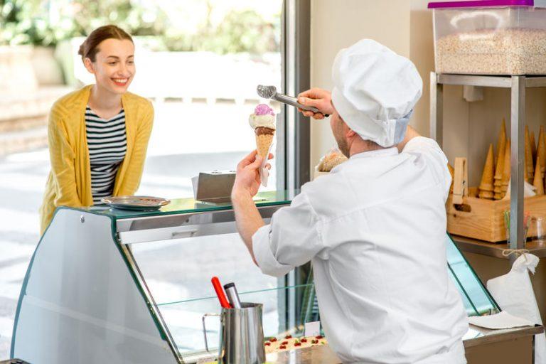 Sorveteiro com colher de sorvete em mãos entrega casquinha com três bolas de sorvete a cliente