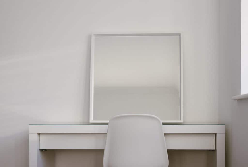 Foto de uma penteadeira branca, com um espelho com bordas brancas e uma cadeira branca.