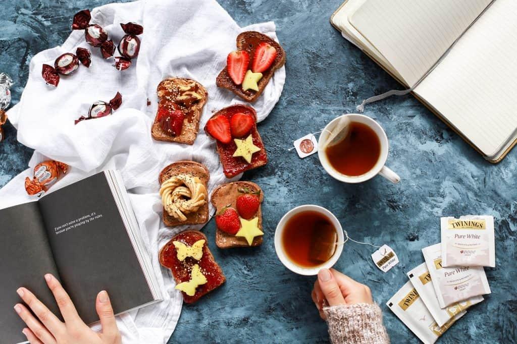 Imagem de mulher tomando chá em xícara de cerâmica sobre mesa com livros, torradas e bombons.