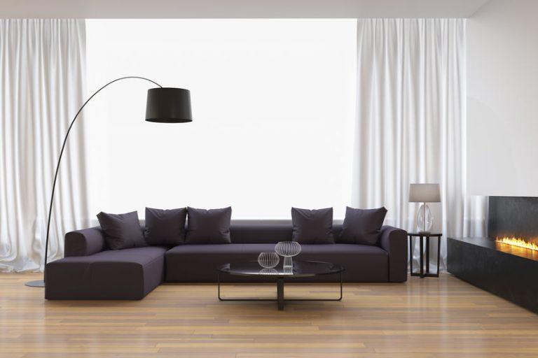 Imagem de sofá de dois lugares em sala de decoração moderna com cadeiras e mesa de vidro