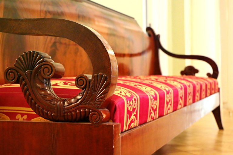 Imagem de sofá de dois lugares com braços de madeira decorados