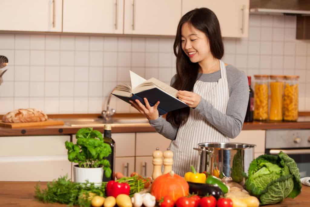 Na foto uma mulher em uma cozinha com diversos ingredientes numa bancada olhando para um livro.